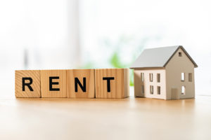 house model near cubes with rent lettering on wooden table